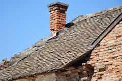Defective chimney flashing, broken tiles, cracked mortar and missing gutter