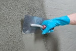 Drybase Universal Mortar being trowelled smooth after spray application onto a wall