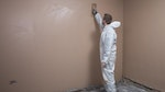 Applying a finishing skim coat on top of the plasterboard