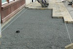 Paving being laid over aggregate and membrane