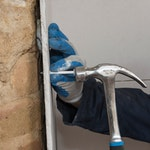 Fix plasterboard to wall with plugs