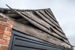 Garage with rustic warped wooden shingle gable end wall
